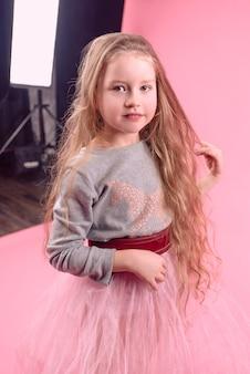 분홍색 배경에 긴 금발 머리를 가진 귀여운 재미있는 어린 소녀