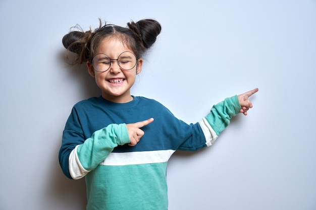 Cute funny little girl with smile and glasses points fingers to the side on empty space for your text or product