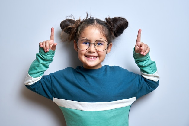 Cute funny little girl with smile and glasses points fingers upwards on empty space for your text or product