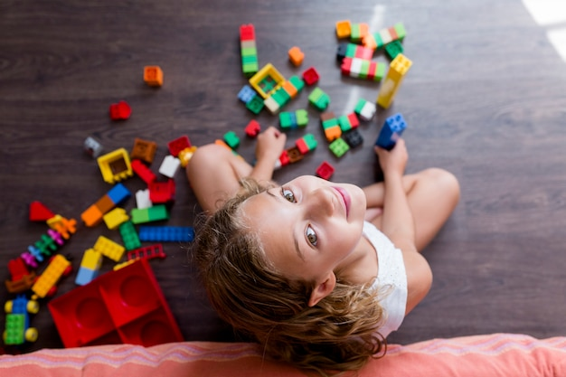 Милая смешная девушка preteen играя с игрушкой конструкции преграждает строить башню дома. дети играют.