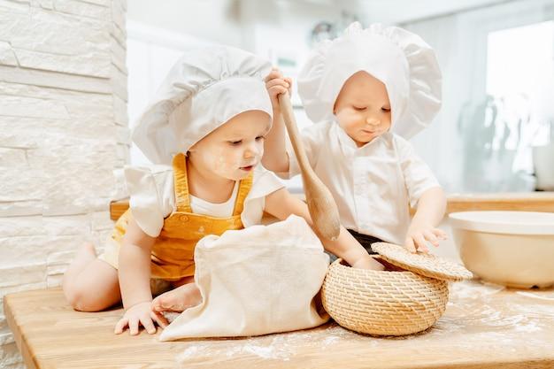 かわいい面白い落ち着きのないポジティブな白人の汚れた子供たちは台所のテーブルでパイを作っています