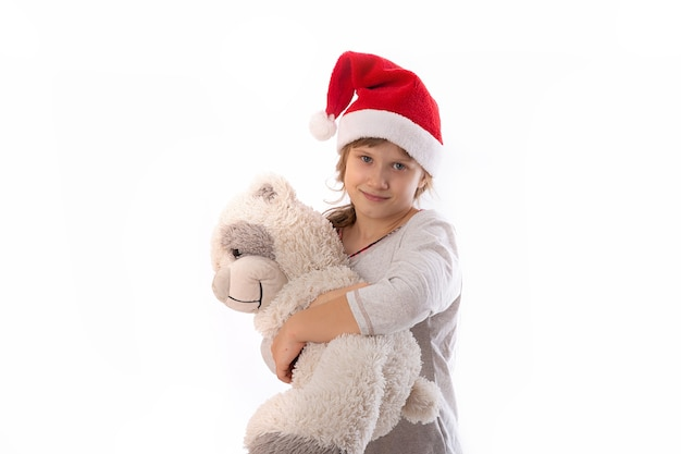 Cute funny santa's helper hold a toy teddy bear on a white background. the concept of christmas holidays.