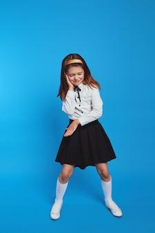 Милая смешная школьница в униформе ведет себя как ди-джей на синем бумажном фоне стены