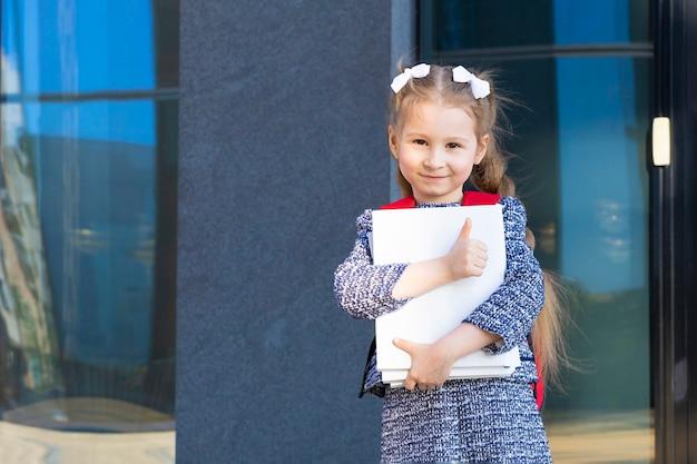 Милая смешная умная школьница с книгами. обратно в школу. счастливый ребенок, умница идет в первый класс.