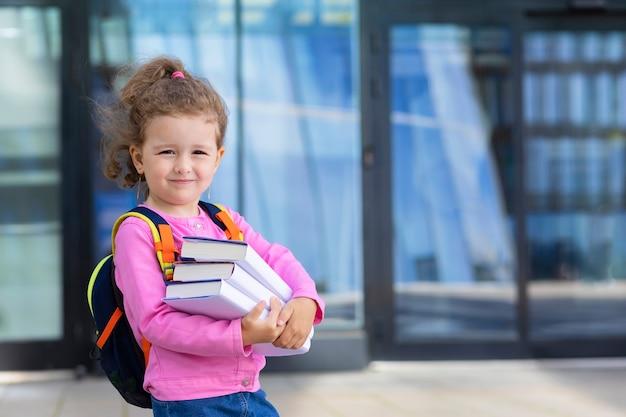 Милая смешная умная школьница с книгами. обратно к школьникам. счастливый ребенок, умница идет осенью в первый класс днем.