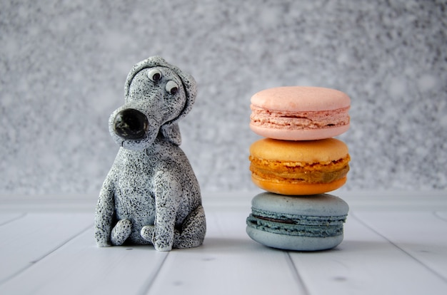 Cute funny toy dog looks at delicious sweet macaroons lying nearby. concept: diet, avoiding sweets, proper nutrition, making confectionery. humorous postcard, poster, space for text