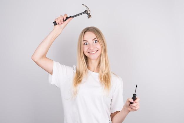 Милая забавная маленькая девочка, держа в руках рабочие инструменты.