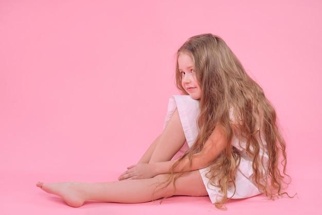 ピンクの背景に座っている白いドレスのかわいい面白い若い女の子