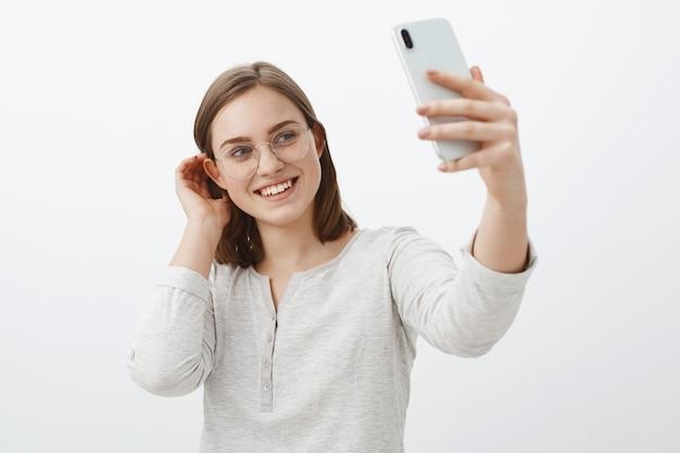 Donna carina e gentile che fa selfie da inviare all'app di appuntamenti in attesa del vero amore, sfogliando una ciocca di capelli dietro l'orecchio e sorridendo teneramente allo schermo dello smartphone in piedi femminile sopra il muro grigio