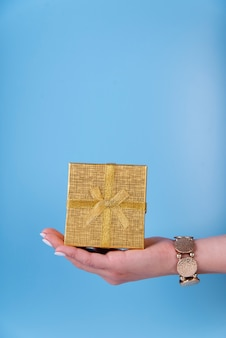 Cute gift box held in hand on blue background