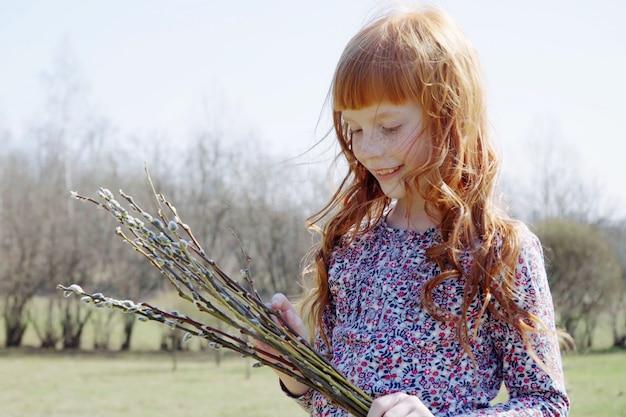 공원에서 가지의 봄 무리를 들고 귀여운 생강 소녀