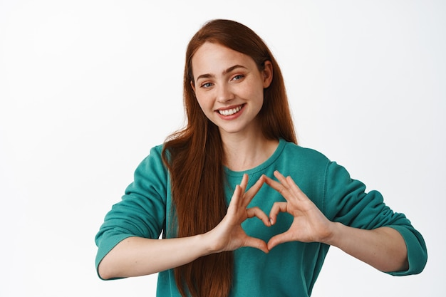 Cute ginger girl shows heart i love you, care for someone, like you, smiling happy, standing on white