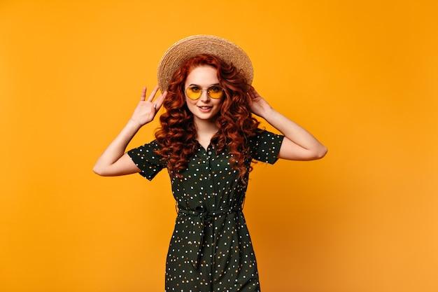 미소로 밀 짚 모자를 만지고 귀여운 생강 소녀. 노란색 배경에 포즈 놀라운 유럽 여자의 전면 모습.