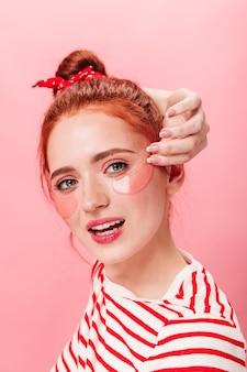 카메라를보고 눈 패치 귀여운 생강 소녀. 분홍색 배경에 부드럽게 미소로 포즈를 취하는 멋진 젊은 여자.