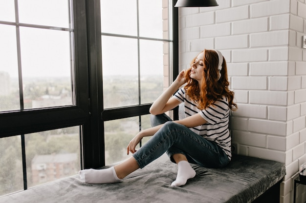 敷居の上に座って音楽を聴いているジーンズのかわいい生姜の女性。ヘッドフォンの窓の横でポーズをとっている巻き毛の女の子を喜ばせます。