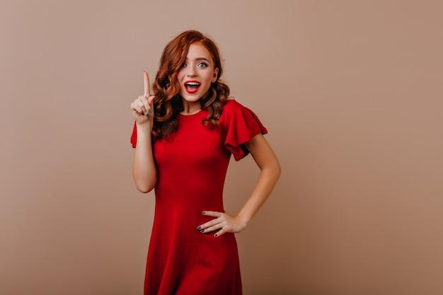 ドレスポーズでかわいい生姜の女性。明るい壁に立っている気さくなヨーロッパの女の子。