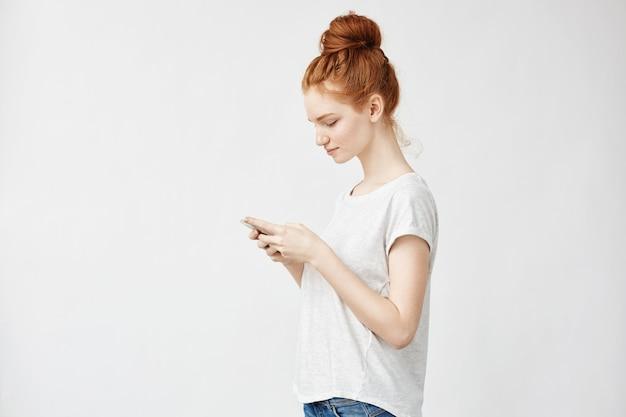 Donna sveglia dello zenzero con le lentiggini che sorride esaminando telefono.