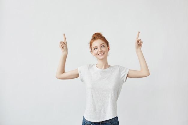 Cute ginger woman with freckles smiling pointing fingers up.