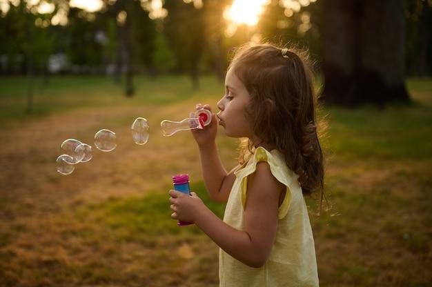 日没時に都市公園の背景にシャボン玉を吹いて、屋外で楽しい時間を楽しんでいる4歳のかわいい女の子。太陽の光線は、虹色の反射を伴う透明な泡球を通り抜けます。