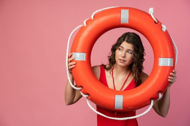 赤い水着を着たライフガードのかわいい女の子が救命浮環を持って、それを通して目をそらします。ピンクの背景の美しい少女