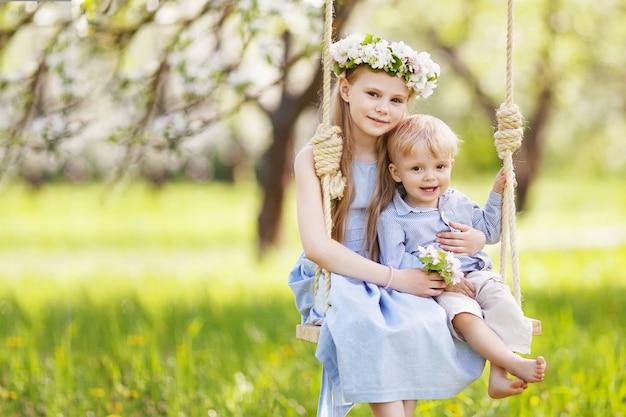 Милая девочка и мальчик, весело проводящие время на качелях в цветущем старом яблоневом саду. солнечный день. весенние мероприятия на свежем воздухе для детей