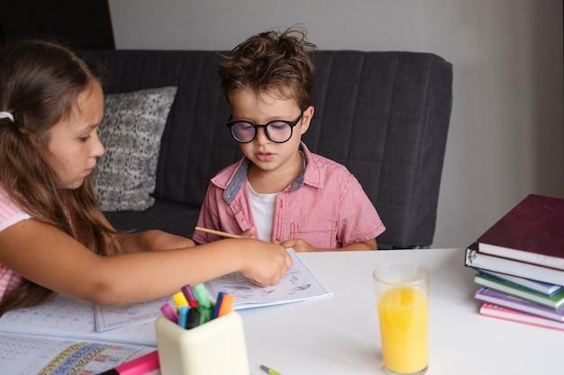 家で勉強している眼鏡のかわいい女の子と男の子は、宿題をします。妹は弟を助けます。兄弟。説明する。リモート教育の概念。検疫。学校のコンセプトに戻ります。