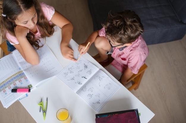 家で勉強している眼鏡のかわいい女の子と男の子は、宿題をします。妹は弟を助けます。兄弟。書き込み。机の上のラップトップ。リモート教育の概念。検疫。学校のコンセプトに戻ります。上面図。