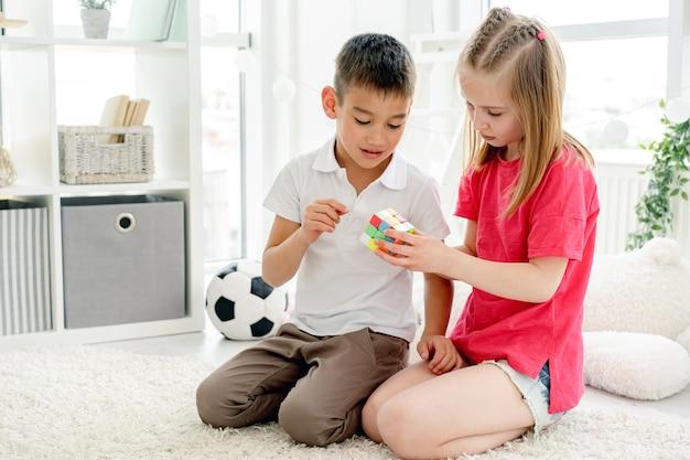 Симпатичные девочки и мальчики играют с кубиком рубика в светлой комнате