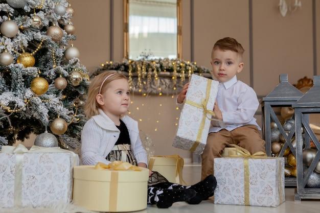 Симпатичная девочка и мальчик, открывающие рождественские подарки. дети под елкой с подарочными коробками.