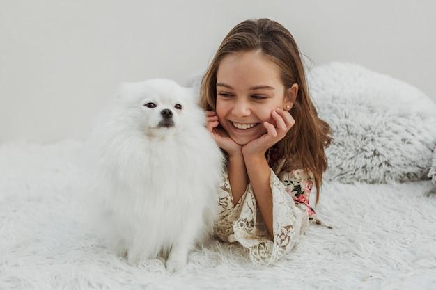 Милая девушка и собака, сидя в постели