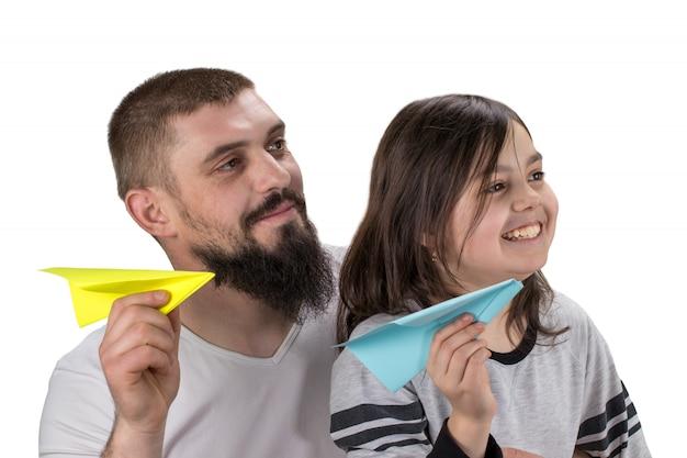 かわいい女の子と父親と白い背景で隔離のおもちゃの紙飛行機で遊んで