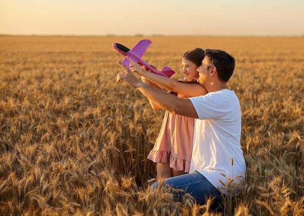 밀밭에서 하늘을 배경으로 장난감 비행기를 가지고 노는 귀여운 소녀와 아버지