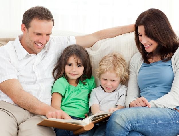 Симпатичная девушка и ее семья, глядя на фотоальбом