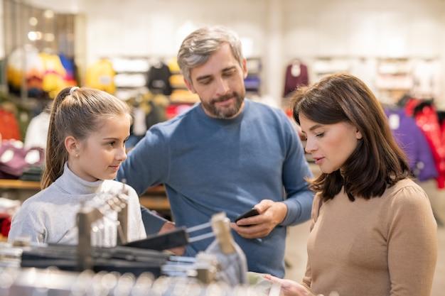 かわいい女の子と彼女の両親は、新しいプルオーバーを選択しながら衣料品部門でカジュアルウェアとラックのそばに立っています。