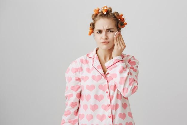 かわいい女の子は寝る前に綿のパッドでクレンザーを塗り、ヘアカーラーとパジャマを着ています