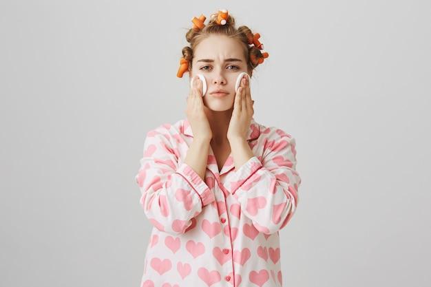 Ragazza carina applica il detergente prima di dormire con un batuffolo di cotone, indossando bigodini e pigiama