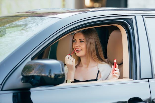 차에 립스틱을 적용하는 귀여운 여자