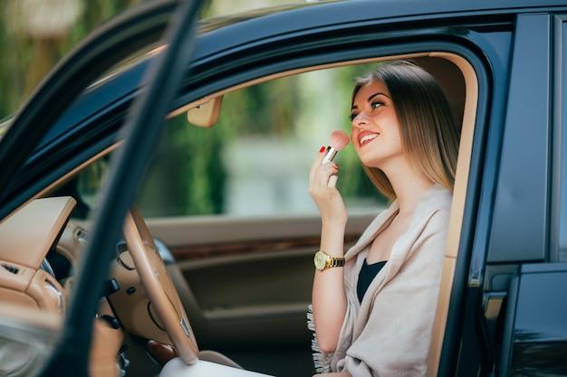 Милая девушка, применяя помаду в машине