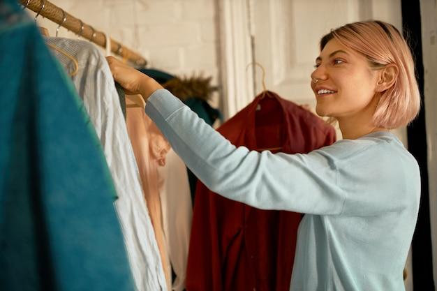Милая девушка расставляет одежду на рельсах с вешалками