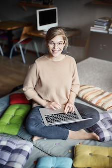 Cute girl asks friend for advice while creating new project. stylish smart woman in glasses with fair hair, holding feet crossed and sitting on laps with laptop, gazing joyfully