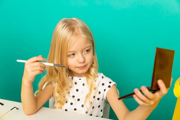Милая девушка дома, говоря перед камерой для видеоблога. маленький ребенок работает блогером, записывает видеоурок для интернета.