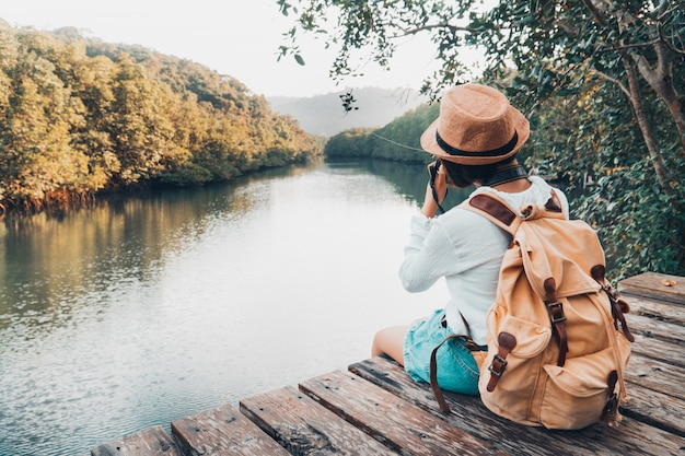 Cute girl backpacking and sitting on the wood plank resting and looking on the river.