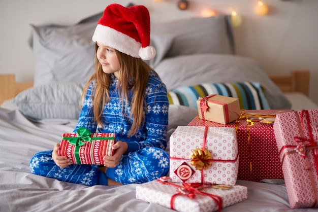 Cute girl in the bed with christmas presents
