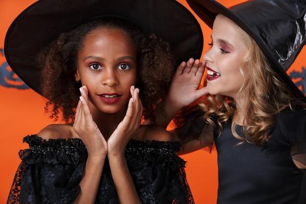Cute girl in black halloween costume whispering secret to friend in her ear isolated over orange pumpkin wall