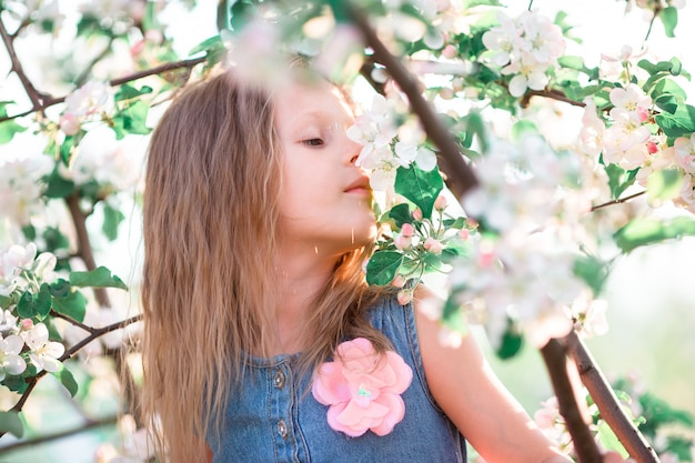 Cute girl in blooming apple tree garden enjoy the warm day