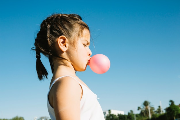 Cute girl blowing bubble gum
