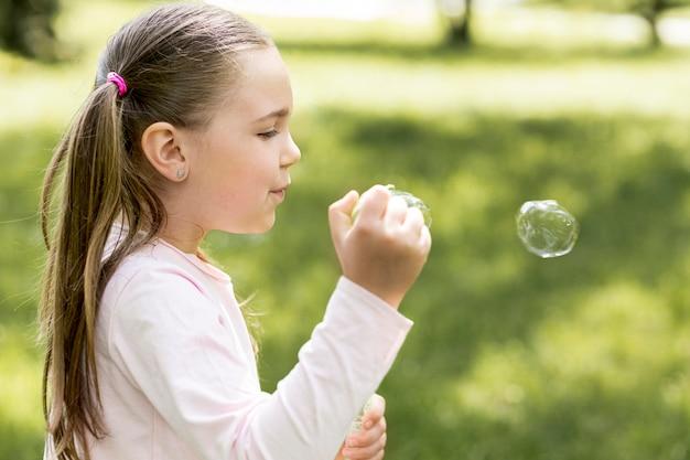 Милая девушка дует пузыри со своей игрушкой