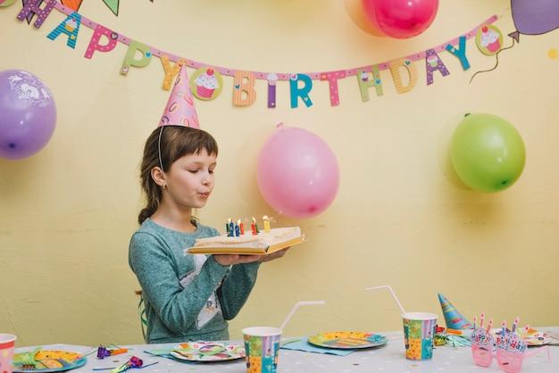Симпатичная девушка дует свечи на торте