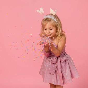 Милая девушка дует конфетти