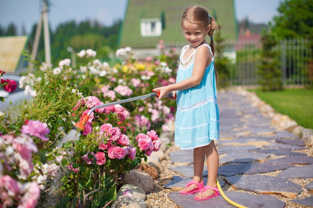 Cute girl in blue dress watering flowers with a hose in her garden